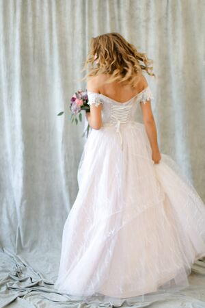 Back view of young bride standing at studio with flowers. Concept of wedding and bridal photo sesion, fashion.