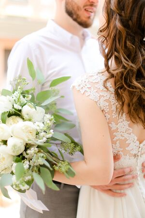 Happy european groom kissing bride keeping bouquet of flowers. Concept of love and wedding photo session.