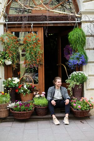 Young man sitting at flower shop near bouquets in baskets. Concept of business adn floristic art.