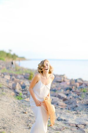 Caucasian smiling girl walking on rocky beach with hant in hands and wearing dress. Concept of summer vacations and fashion.