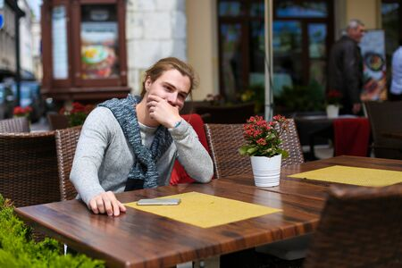 Young businessman sitting at street cafe and wearing grey sweater. Concept of resting and urban lifestyle.