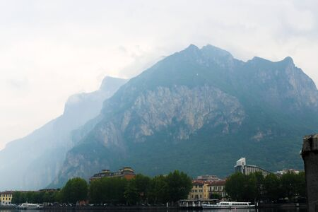 Appenine mountains in fog, coastline with buildings and trees near lake Como. Concept of morning landscape os italian rural places, traveling and summer vacations. Stok Fotoğraf