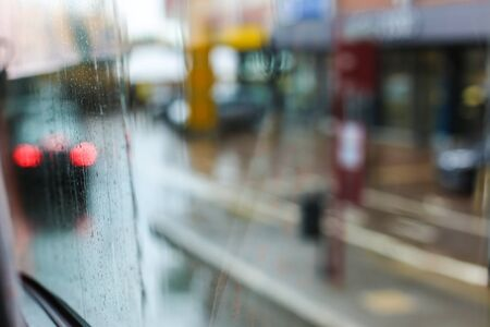 Rainy glass and street lights in background. Concept of rain in town, blurred street. Stock fotó