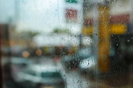 Rain drops on glass and street cars in background. Concept of rain in town, blurry image. Stock fotó
