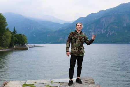 Happy young man wearing camouflage jacket standing with lake Como and mountain in background. Concept of tourism and nature, Mediterranean.