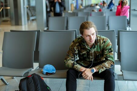 Caucasian male student sitting in waiting room at airport and listening to music with white earphones, wearing camouflage shirt. Concept of traveling and cheap tickets, law cost flights.