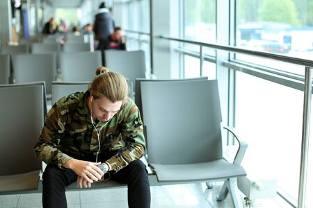 Young man wearing camouflage shirt, sitting in waiting hall at airport near window, listening to music with white earphones and looking at watch. Concept of low cost flights and traveling.