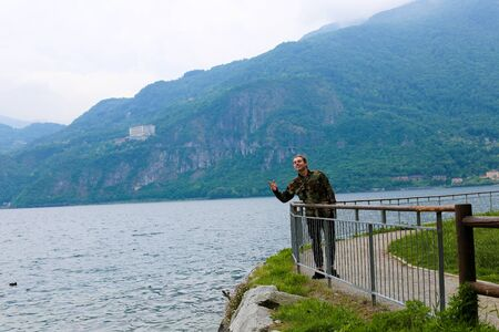 Caucasian tourist wearing camouflage jacket standing near banister,lake Como and mountain in background. Concept of traveling to Italy and tourism. Stok Fotoğraf