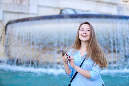 Young caucasian student chatting by smartphone in Trevi fountain background. Concept of modern technology, advantageous tariff plan and summer vacations in Europe.