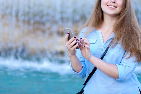Young caucasian woman chatting by smartphone in Trevi fountain background. Concept of modern technology, advantageous tariff plan and summer vacations in Europe. Standard-Bild