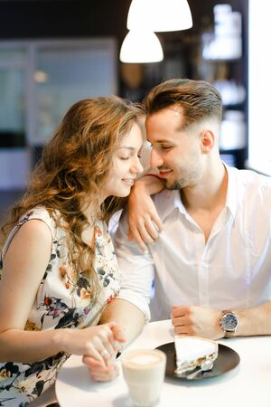 Young european woman and man having lunch at cafe, resting and drinking coffee. Concept of of love, catering establishment and happy couple. Stok Fotoğraf
