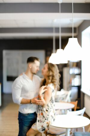 Soft focus photo of young caucasian couple standing at cafe and hugging. Concept of togetherness and love. 版權商用圖片