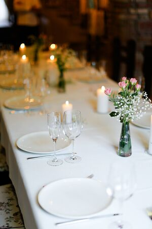 Bouguet of flowers, plates with forks and white candles on table. oncept of romantic dinner and catering establishment.