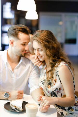 Young lovely woman and man having lunch at cafe, resting and drinking coffee. Concept of of love, catering establishment and happy couple.