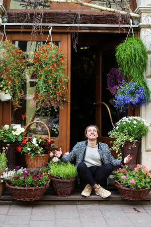Young male person sitting at flower shop near bouquets in baskets. Concept of business adn floristic art.