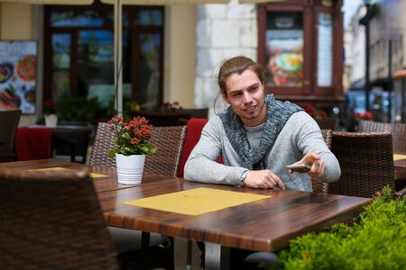 Young caucasian man sitting at street cafe and wearing grey sweater. Concept of resting and urban lifestyle. Reklamní fotografie