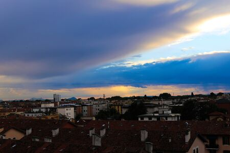 Charming cityscape in sunset backgound. Concept of dusk and summer cloudscape in city. Stock Photo