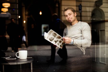 Young man reading menu at cafe with cup of coffee on table, reflection in window. Concept of resting with tea, tourist having lunch.
