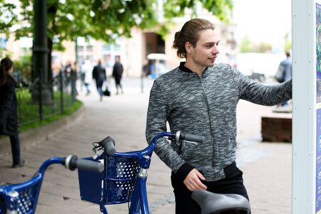 Young boy hiring blue bicycle in city. Concept of urban lifestyle, ecology and bike hire vending machine.