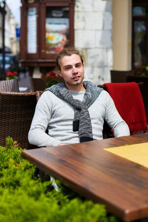 Young man sitting at street cafe near green plants, wearing grey sweater. Concept of resting in open air and waiting lunch.