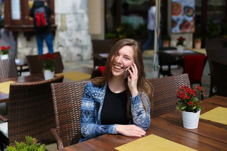 Young smiling female person speaking by smartphone at cafe near red flowers. Concept of modern technology and advantagous tariff plan.
