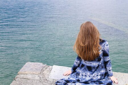 Back view of young woman sitting near lake Como, water in background. Concept of summer vacations. 写真素材