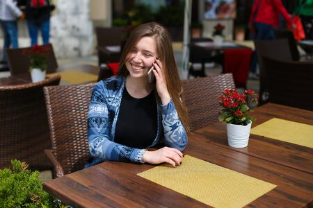 Young female person speaking by smartphone at cafe near red flowers. Concept of modern technology and advantagous tariff plan.