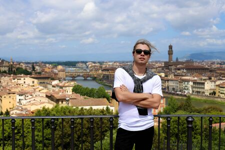 Man standing on balcony with Florence cityscape background. Concept of last minute cheap tours to Italy and summer vacations in Europe. Stok Fotoğraf