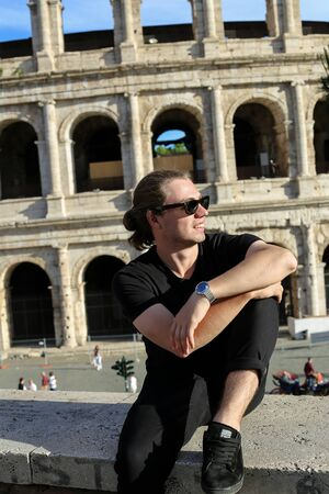 Young caucasian male tourist in glasses sitting in Colosseum background in Rome, Italy. Concept of last minute tours to ancient Europe and low cost flights.