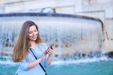 Young caucasian girl chatting by smartphone in Trevi fountain background. Concept of modern technology, advantageous tariff plan and summer vacations in Europe.