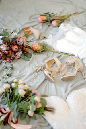 Fashionable bridal shoes and flowers. Concept of fiancee wear and wedding photo session.