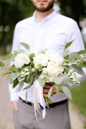 Caucasian groom wearing grey trousers and white shirt waiting for bride with bouquet of flowers. Concept of wedding photo session and floristic art.