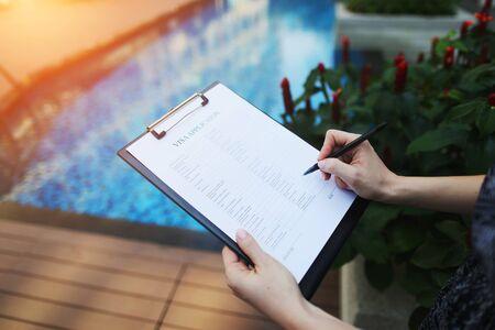 le mani della donna firmano o compilano il modulo di domanda di visto per la Francia sullo sfondo della nuova piscina. concetto di viaggio d'affari, un appello agli agenti di viaggio per l'organizzazione del tour. Frontale utilizzato con licenza Open Font Archivio Fotografico