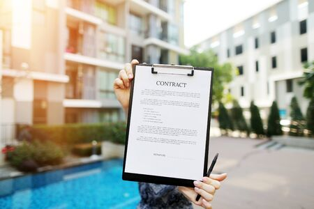 Focus on contract, girl is holding document on background of building and proposes to sign contract, focus on doc. concept of agents for delivery of real estate, an agreement between people on lease. Front used with Open Font License
