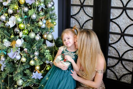 Young blonde mother and little daughter wearing dress standing near Christmas tree. Conceptof celebrating New Year and winter holidays, seasonal atmosphere and fashion.