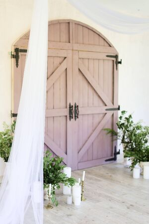 Two candles near wooden gate and plants. Concept of wedding decorations.