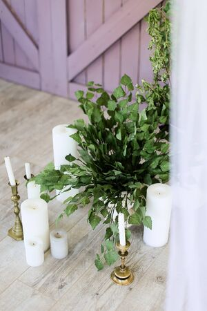 White candles near wooden door and plants. Concept of wedding decorations.