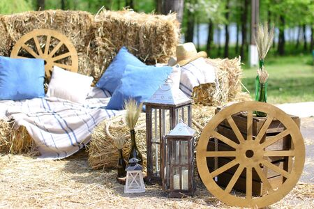 Wooden wheel with pillows, hats and bottles with wheat ears. Concept of summer vacations on farmland.