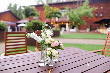 Flowers in vase on wooden table. Concept of restaurant and catering establishment.