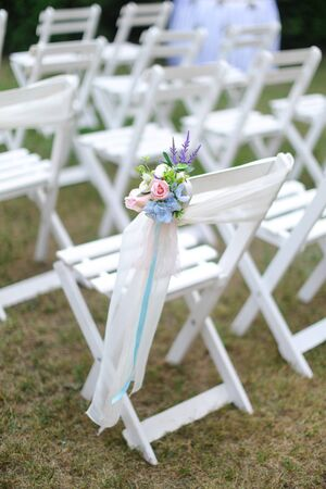 White chairs on green grass background. Concept of wedding seating places.