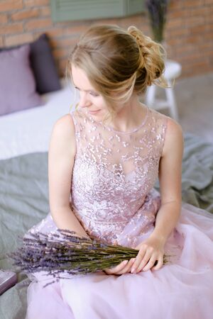 Blonde fiancee sitting with lavander bouquet at home. Concept of bridal photo session in provans way.