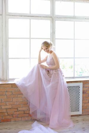 Blonde bride wearing dress and standing near window and dreaming. Concept of bridal photo session and nice fiancee.