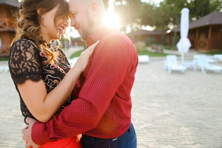Bald european man wearing red shirt and hugging woman. Concept of relationships and romantic love. Reklamní fotografie