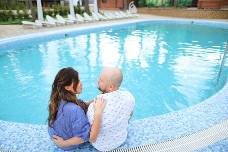 Bald husband and wife sitting barefoot near swiming pool. Concept of happy couple and summer vacations on resort.