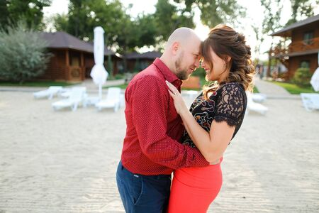 Bald caucasian husband wearing red shirt and dancing with wife on backyard. Concept of weekends and resting, relationships and happy couple. Reklamní fotografie