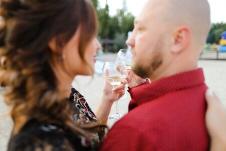 Bald husband wearing red shirt dancing with wife and drinking wine. Concept of leisure time, romantic love and weekends. Reklamní fotografie