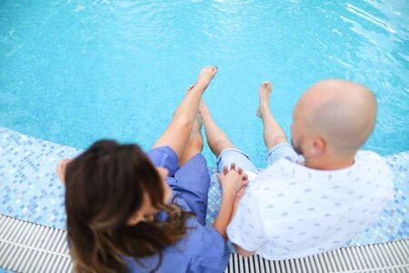 Husband and wife sitting barefoot near swiming pool. Concept of happy couple and summer vacations on resort.
