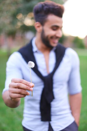 Blurred photo of hispanic male person blowing dandelion. Concept of male person in green background.