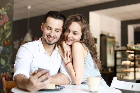 Young wife sitting with husband using smartphone at cafe and eating cake. Concept of food and drink, happy couple and relationship, modern technology. Stock Photo