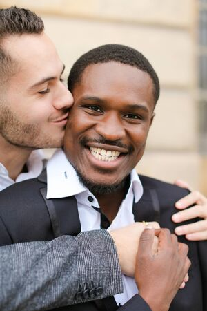 Portrait of caucasian man kissing afroamerican boy. Concept of gays and happy same sex couple.